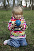 The little girl is considering a ball — Stok fotoğraf