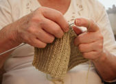 Hands of an elderly woman knitting — Stock Photo