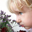 Stock Photo: Little girl smelling flowers