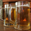 Two mugs of beer on a wooden table — Stockfoto