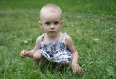 A little girl sitting in the grass — Stock Photo