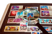 Stamp album and magnifying glass — Stock Photo