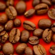Coffee beans on red background - Stock Photo