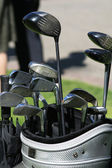 Golf clubs and umbrella in the bag — Stock Photo