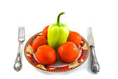 Peppers and tomatoes on plate on white bacground — Stock Photo