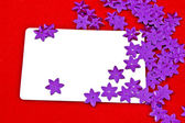 White card and violet stars on red background — Stock Photo