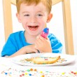 Boy decorating baked biscuits — Stock Photo #2961306