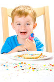 Boy decorating baked biscuits — Stock Photo