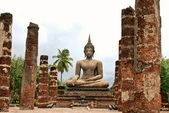 Buddha in the ruins of Wat Mahathat — Stock Photo