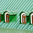 Roof dormers on the roof covered with green iron plates - Stock Photo