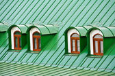 Roof dormers on the roof covered with green iron plates — Stock Photo