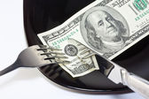Banknote on a black plate with knife and fork — Stock Photo