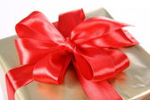 Gift in golden wrapping with red bow — Stok fotoğraf