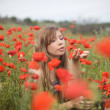 Beautiful young blond woman in poppy fie - Stock Photo