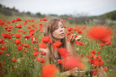 Beautiful young blond woman in poppy fie — Stock Photo