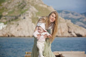 Beautiful young mom with a baby for a wa — Stock Photo