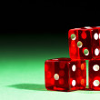 Three red dices on green — Stock Photo