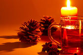 Red tea cinnamon sticks star anise conifer cone at candle light — Stock Photo