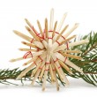 Straw star in front of a branch - Stock Photo