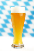 Wheat beer with bavarian background — Stock Photo