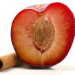 Half wet plum with a cinnamon stick — Stock Photo
