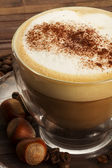Cappuccino with hazelnuts on wooden background — ストック写真