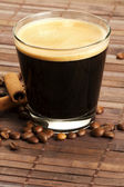 Espresso in a short glass with coffee beans and cinnamon from diagonal top — Stock Photo