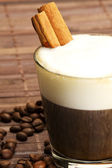 Espresso in a short glass with milk froth and cinnamon inside — Stock Photo