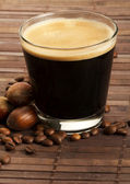 Espresso coffee in a short glass with hazelnuts — Stock Photo