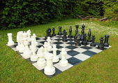 Big outdoor chess in green lawn — Stock Photo