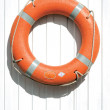 Orange lifebuoy on fence - Stock Photo