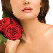 Woman with red roses on neck — Stock Photo