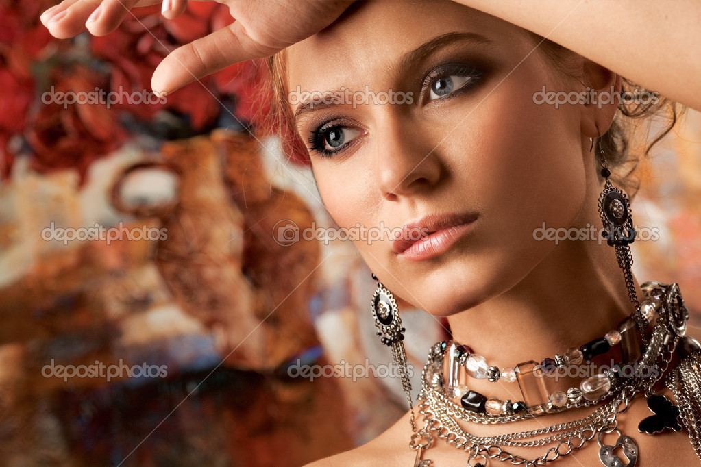 A portrait of a young glamorous woman wearing stylish necklace and pierced earrings.   #3042140