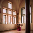 Woman playing guitar in Malbork Castle. - Stock Photo