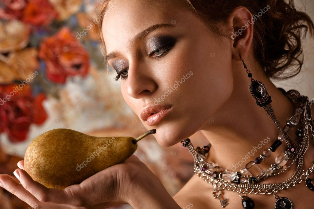 A close-up of a beautiful elegant woman holding a pear on her palm. — Stock Photo #3849383