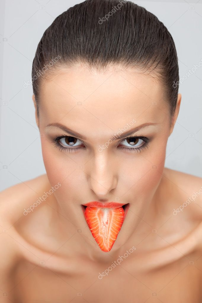 Portrait of a young pretty lady with a fresh strawberry in her mouth. — Stock Photo #3849499