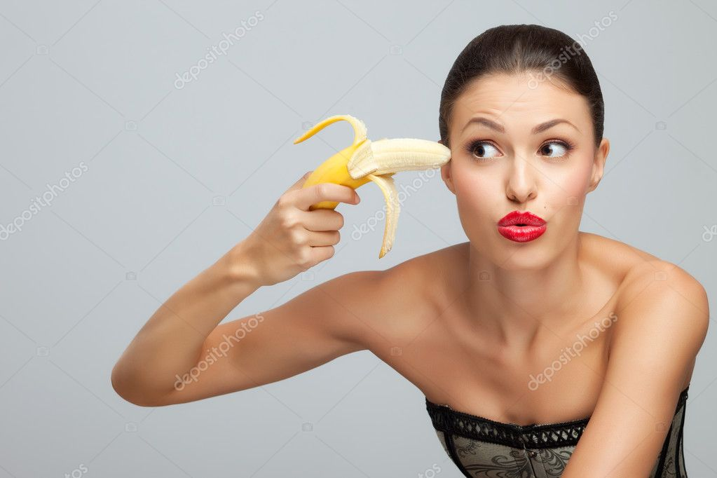 A portrait of a beautiful sexy lady trying to kill herself with banana.  Stock Photo #3849616