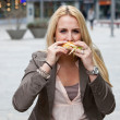 Beautiful girl having a burger — Stock Photo