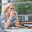Pretty blond girl eating a bagel — Stock Photo