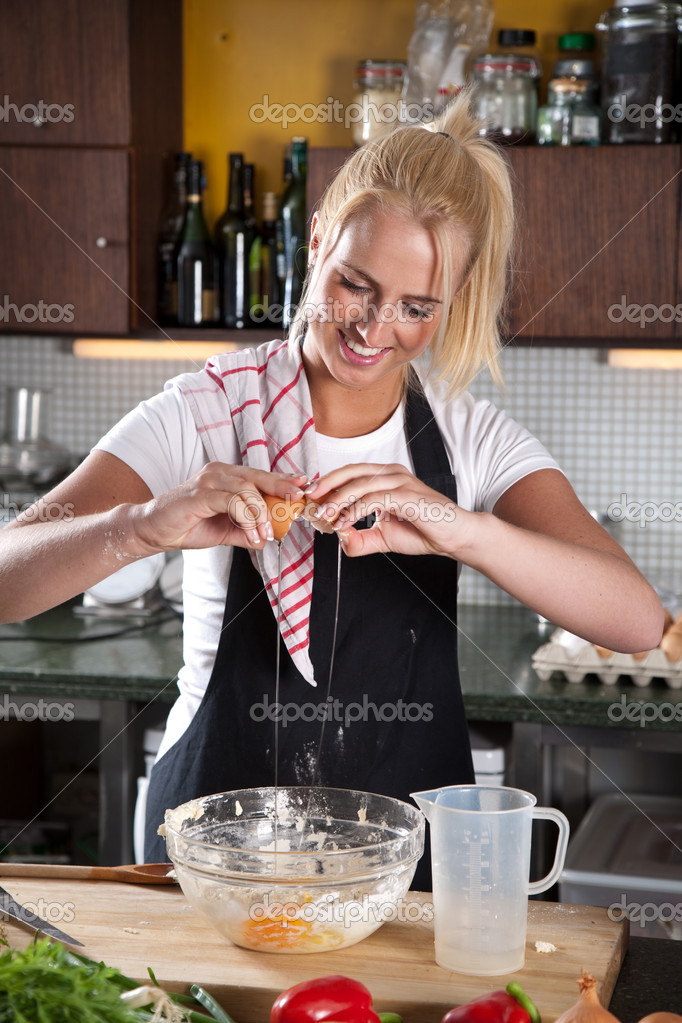 Beautiful young chef adding an egg to her dough — Stock Photo #2948358