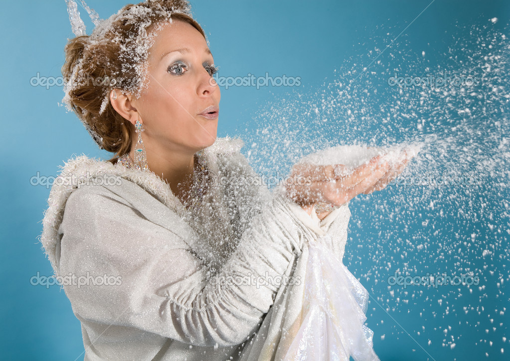 Beautiful blond woman dressed in an elegant robe blowing snow from her hands — Stock Photo #2948769