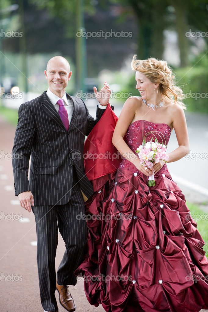 Pretty wedding couple walking while the man is holding her dress — Stock Photo #2949233