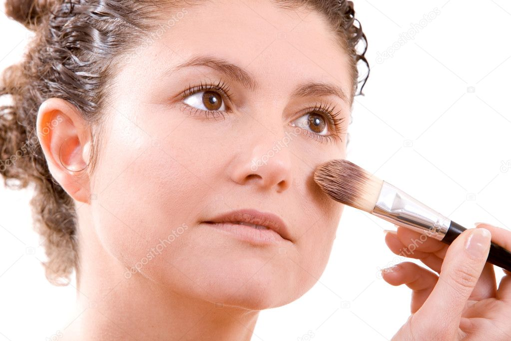 Pretty brunette applying foundation with a big brush — Stock Photo #2949434