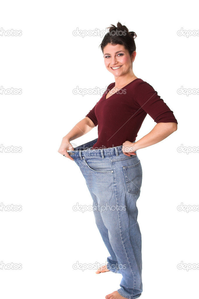 Pretty brunette holding out her old jeans who are now too wide — Stock Photo #2949489