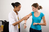 Checking her patient's arm — Stock Photo