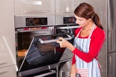Checking the oven — Stock Photo