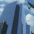 Постер, плакат: Warplane Flying Over Skyscraper