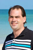 Casual dark haired man at beach — Stock Photo