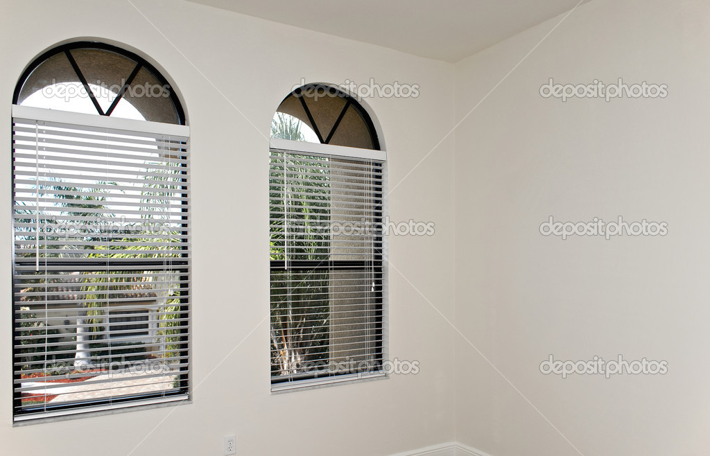 An empty room with two arched windows revealing palm trees outside  Photo #3100145