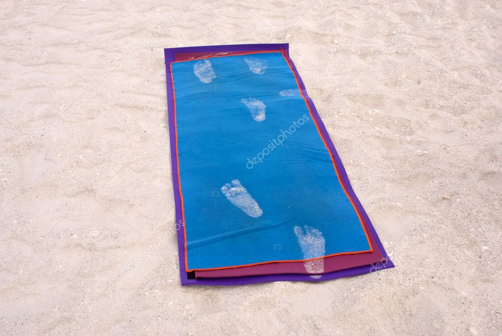 A yoga exercise mat is laid out on the beach and has footprints of sand on it.  Foto de Stock   #3100268